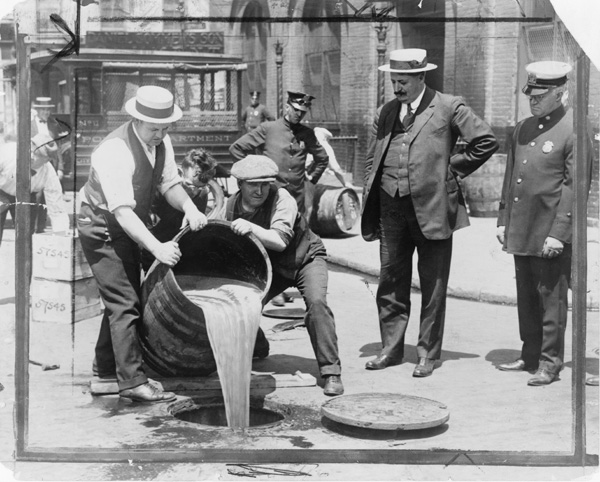 New York City Deputy Police Commissioner John A. Leach, right, watching agents pour liquor into sewer following a raid during the height of prohibition