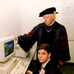 Walter Annenberg in academic regalia and a Peddie School student using the computer the day of a ceremony on campus honoring Ambassador Annenberg, ca. 1993